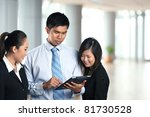 Three Asian business people looking at the screen of Digital Tablet - stock photo