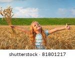 Golden hair girl in wheat field enjoying the setting sun's light at summertime - stock photo