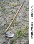 A hoe (garden tool) with land and weeds as background. - stock photo