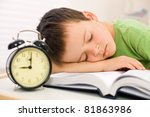 Past bedtime for little schoolboy - asleep on his book - stock photo