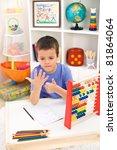 Little boy preparing for elementary school doing simple math exercises - stock photo