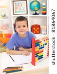 Boy preparing for elementary school doing exercises at home - stock photo