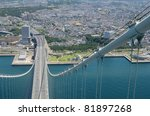 Cable of Akashi Kaikyo Bridge and Kobe City, Japan viewed from 300m above sea level - stock photo
