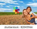 Woman and little girl having fun outdoors with a windmill toy - stock photo
