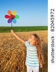 Little girl playing outdoors in summer time with a windmill toy - stock photo