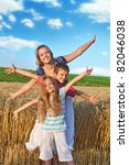 Woman and kids having fun in the wheat field in summer time - stock photo