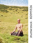 Man meditating at the foot of the mountain - stock photo