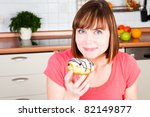 young woman enjoying a  doughnut - stock photo