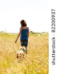 child walking with her dog on a trail - stock photo