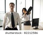 A female office employee swings a keyboard to mock hit her male boss over the head. - stock photo