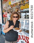 Small photo of BROOKLYN, NEW YORK - JUL 18: A woman eating a knish at a restaurant on Coney Island boardwalk a popular beach and tourist area on the Atlantic Ocean in southern Brooklyn New York, July 18, 2010.