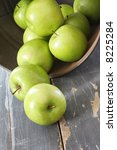 Green Granny Smith apples, spilling from a rusted bucket onto weathered timber table. - stock photo