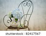 Still Life with Hortensia Flowers in old vase on retro Chair - stock photo