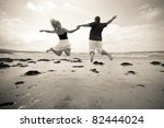 Happiness jump of young couple on the beach - stock photo