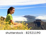 Hiker woman looking at view sitting on mountain top. Hiking on the peak of La Palma (Roque de los Muchachos), Canary Islands - stock photo