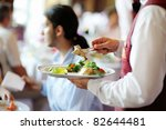 Waiter carrying a plate with meat dish - stock photo