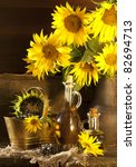 Jug and bottle of sunflower oil with flower - stock photo