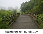 """""""Footbridge Panorama""""  A panoramic view of a wooden footbridge in Monmouth Battlefield State Park in New Jersey on a fogy Summer morning. - stock photo"""