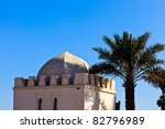 Marrakesh, Morocco:  Whitewashed exterior of traditional domed building and palm tree in Marrakesh, Morocco. - stock photo