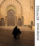 Casablanca, Morocco:  Silhouette of woman in burka and child walking toward Hassan II Mosque in Casablanca, Morocco. - stock photo