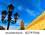 Marrakesh, Morocco:  Street lamp and exterior mosque wall with minaret Marrakesh, Morocco. - stock photo