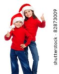 Two smiling little children with thumbs up sign and Santa's hats, isolated on white - stock photo