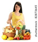 Young woman with groceries in wicker basket isolated on white. Variety of products including vegetables, fruits, dairy, wine and bread - stock photo