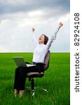 happy businesswoman with computer sitting on chair over green field - stock photo