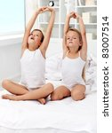 Kids waking up and stretching their arms on the bed - stock photo