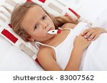 Sick and sad kid in bed holding thermometer between lips - stock photo