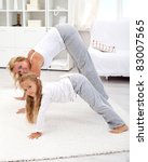 Little girl at home stretching with her mother in the morning - focus on the kid - stock photo