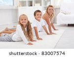 Kids having fum doing some morning gymnastic with their mother at home - focus on the little girl - stock photo