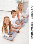 Happy smiling kids doing yoga relaxation at home with their mother - focus on the little girl - stock photo
