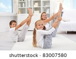 Healthy morning stretching - woman with kids doing gymnastic exercise at home - stock photo