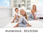Kids and woman at home doing stretching yoga exercises - focus on the little girl - stock photo