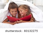 Enjoying the forbidden knowledge - kids reading in bed under the quilt - stock photo