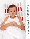 Sick boy in bed holding thermometer between lips - stock photo