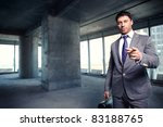 A man in a suit with a briefcase at a construction site - stock photo