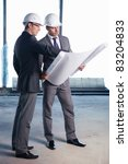 Businessmen held on site plan - stock photo