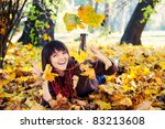 Smiling happy girl, playing with autumn leaves. Outdoor. - stock photo