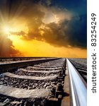 railway to horizon under dramatic sky with sun - stock photo