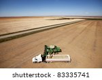 A combine unloading a harvest of lentils onto a truck on the prairie - stock photo