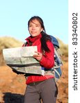 Hiking woman in nature holding map outdoors in nature. Smiling happy hiker in desert mountain landscape. - stock photo