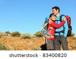 Happy couple healthy lifestyle affectionate outdoors in nature during hiking travel. Man and woman hikers smiling in mountain desert landscape. - stock photo