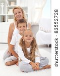 Happy woman and kids sitting in the living room smiling - stock photo