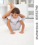 Little contortionist boy bending himself in his room - stock photo