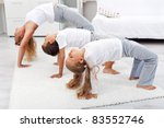 Woman and kids doing bridge stretch gymnastic exercises at home - stock photo
