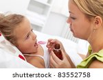 Little girl in bed taking medicine with plastic spoon - stock photo