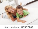 Happy mother and son playing in the living room wrestling on the floor - stock photo