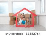 New home concept - people in empty room with cardboard boxes and house shaped frame - stock photo